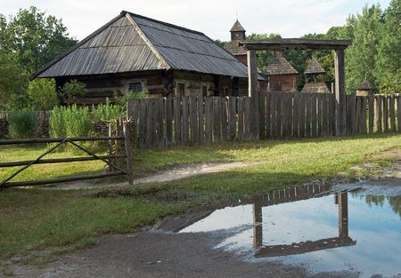 land hout hoeve en boog Repulse in plas (met de kerk achter, stomp bijenkorf in de binnenplaats), (vorige eeuw, museum van de Oekraïense volk architectuur in Pirogovo dorp (in de buurt van Kiev))