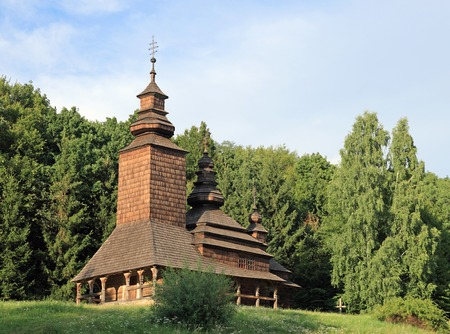 Ukrainian historical country wood church on forest edge photo