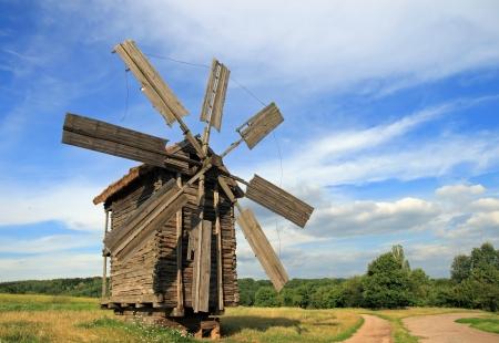Oud historisch achterhaalde windmolen nabij land weg in veld Stockfoto