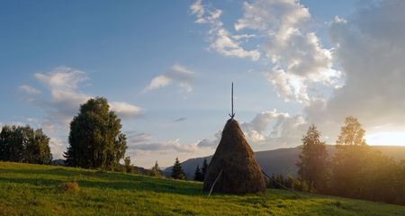 Sunset on summer mountainous green meadow with stack of hay (Slavske village, Carpathian Mts, Ukraine). Five shots composite picture. photo