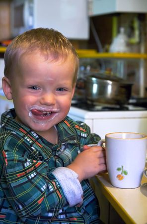 fare: mischievous to lick lips small boy satisfied with cup of dairy product Stock Photo