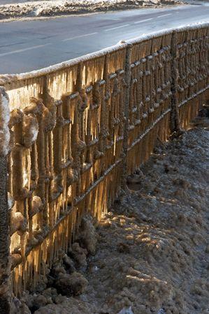 slush: Texture de la ville d'hiver de transport - route gla�age garde-corps (� partir de l'autoroute de neige fondante) et la lumi�re du soleil gr�ce � gla�ons