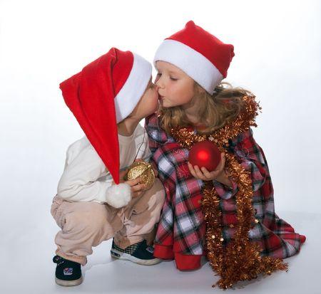 Los pequeños besos niños y niñas antes de la Navidad (a la luz de fondo - no aislada)  Foto de archivo - 2214600