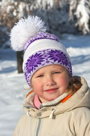 Portret of small girl in winter snow covered city park photo