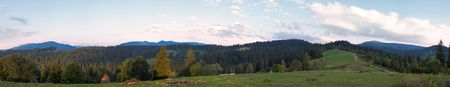 ultramarine: Summer evening twilight panorama view with green pasture meadow and ultramarine color distant ridge (Slavske village outskirts, Carpathian Mts, Ukraine).Twelve shots composite picture. Stock Photo