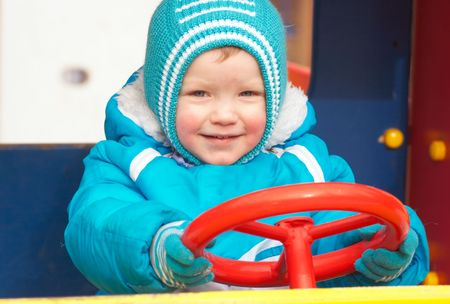 Little boy is learning to drive on the pleasure-ground.  photo