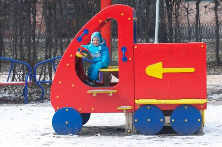 Little boy is learning to drive on the winter pleasure-ground in park.  photo