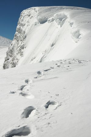 steep cliffs sign: Winter steep crag and human footprint on snow follow to the precipice (Ukraine, Carpathian Mts, Svydovets Ridge, Blyznycja Mount)
