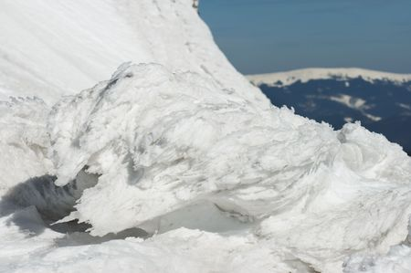 brink: Wind form ice lumps on precipice brink and winter mountain behind (not in focus) Stock Photo