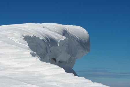 steep cliffs: Fairy figure overhang snow cap formed on blue sky background