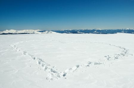 mountainside: Human footprint form the heart shape on snow-covered mountainside plateau and mountain ranges behind Stock Photo