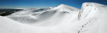 Winter mountains ridge with overhang snow caps and snowboard tracks on blue sky background (Ukraine, Carpathian Mts, Svydovets Range, Blyznycja Mount, Drahobrat ski resort). Seven shots stitch image. photo