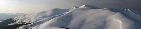 mountainside: Snow-covered mountain ridge in first daybreak sun rays pastel illumination - day-to-night transition (Ukraine, Carpathian Mts, Svydovets Range). Nine shots stitch image.