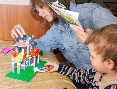 Mother with small son play with building set for children (built a house) photo