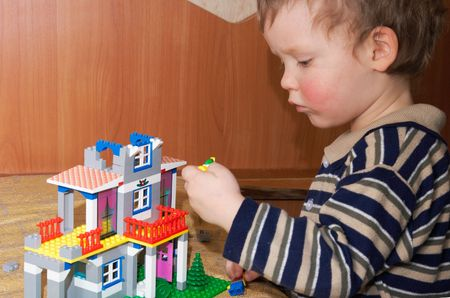 certitude: Small boy play with building set for children (built a house) Stock Photo
