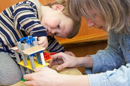 certitude: Mother with small son play with building set for children (built a house)