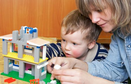 Mother with small son play with building set for children (built a ) photo
