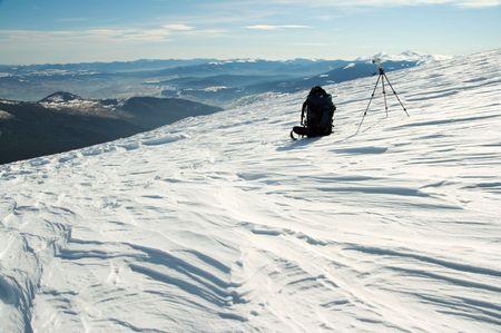 mountainside: Winter mountain landscape with tourist knapsack and photographic tripod (Ukraine, Carpathian Mts, Goverla and Petros Mountains behind) Stock Photo