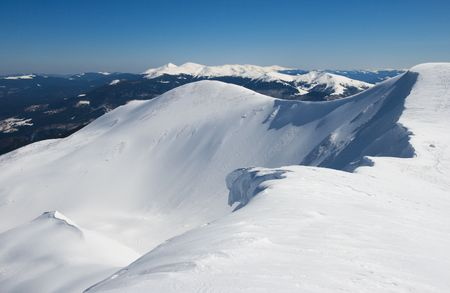 overhang: Winter mountains ridge with overhang snow caps and snowboard tracks on blue sky background (Ukraine, Carpathian Mts, Svydovets Range, Blyznycja Mount, Drahobrat ski resort)