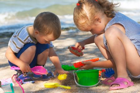 sandbox: Small girl and boy play with sand near sea Stock Photo