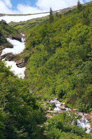thawing: thawing the rest of the snow on summer mountainside Stock Photo