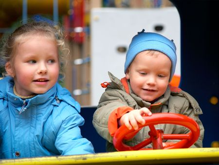Little boy is learning to drive on the pleasure-ground and his sister photo