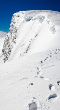 steep cliffs sign: Winter steep crag and human footprint on snow follow to the precipice (Ukraine, Carpathian Mts, Svydovets Ridge, Blyznycja Mount). Four shots stitch image.