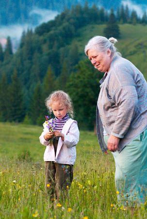 recolectar: Ni�a con su abuela recoger flores de campo en las laderas de las monta�as Foto de archivo
