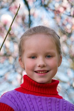 Happy small girl portrait near blossoming magnolia tree photo