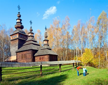 Ukrainian historical country wood church on forest edge and mother with small children near Stock Photo - 4775043