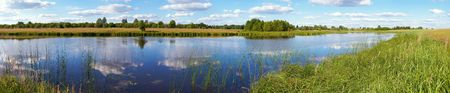 Summer rushy lake panorama view with clouds reflections. Eleven shots composite picture. photo