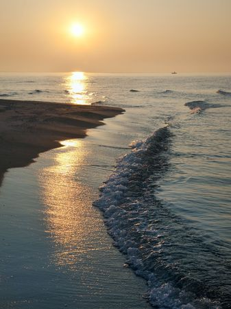misty daybreak sea sandy shore with sunlight path and fishing boat distant silhouette Stock Photo - 4911287