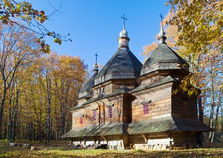 Ukrainian historical country wood church on forest edge in mountain photo