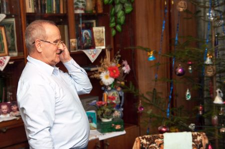 celebratory event: mature age man making Christmas congratulations by phone