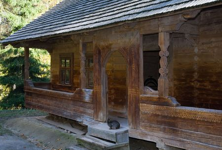 woodcarving: Ukrainian historical country wooden hut with woodcarving and cat on entrance threshold