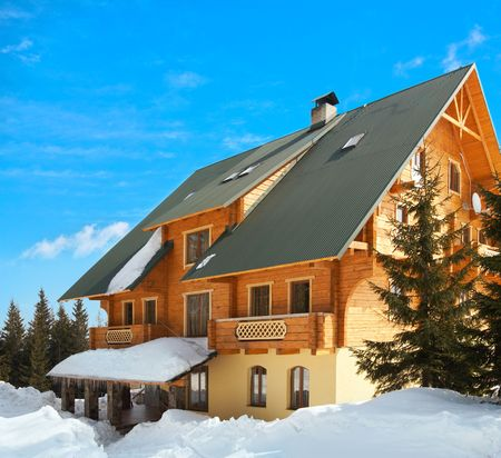 Wonderful wood house on picturesque winter resort place on blue sky background photo