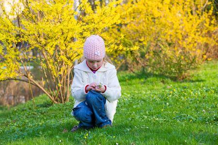 recolectar: La ni�a peque�a feliz reunir gowan flores cerca de arbusto floreciente de Forsythia amarillo  Foto de archivo
