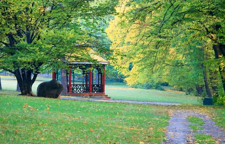 Wooden belvedere, big stone and pedestrian path  in autumn city park photo