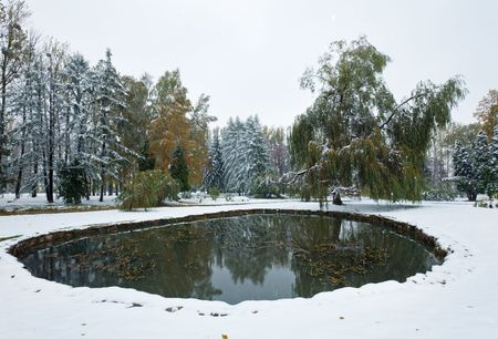 sudden: First autumn sudden snow in city park and small pond