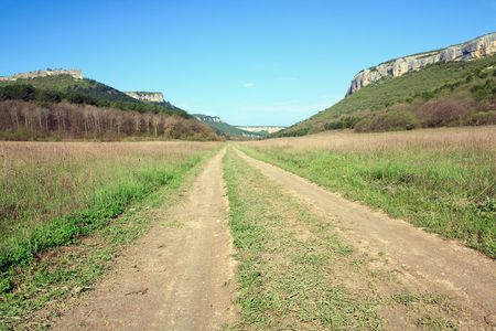 Spring Crimean mountain landscape and rural roads in valley (Mangup Kale - historic fortress and ancient cave settlement in Crimea, Ukraine) photo