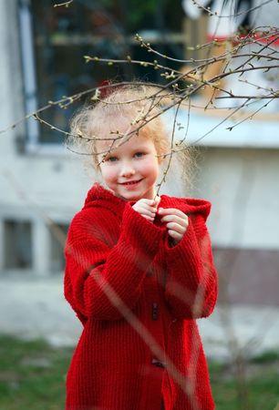 impish: Smiling happy little girl in spring garden near her home