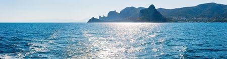 scintillate: Scintillate la superficie del mar y la costa rocosa de noche verano (Crimea, Ucrania). Cuatro disparos unir la imagen.