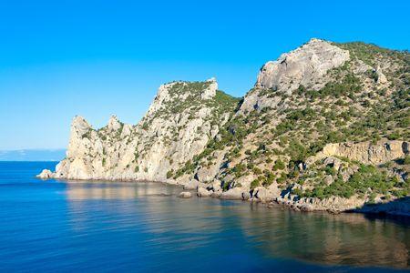 rocky mountain juniper: Summer rocky coastline with juniper trees (Novyj Svit reserve, Rhinoceros cape, Crimea, Ukraine).