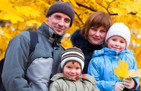 Jonge familie (ouders met kleine kinderen) in gouden herfst stads park  Stockfoto