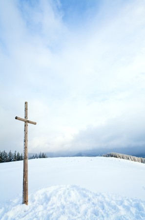 winter snowy fir trees on mountainside on overcast sky background and wooden cross in front (Carpathians, Ukraine) photo