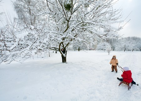 Happy family (mother with small boy and girl) in winter city park photo