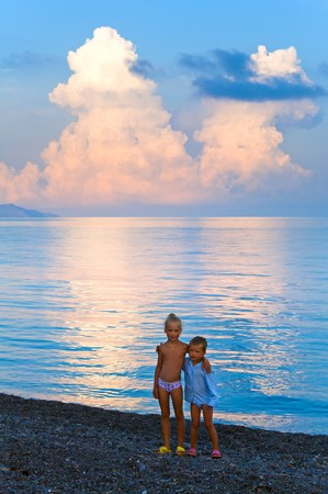 stony: Beautiful sunset in soft pink-blue colors, shining sea surface and  children on beach (Crimea, Ukraine). Stock Photo