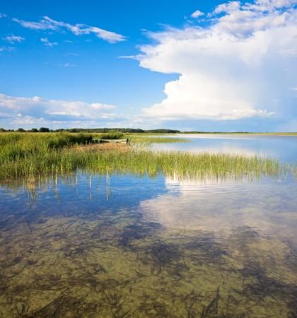 Zomer panorama uitzicht op het meer met wolken reflecties en houten boot. Twee schoten steek beeld.