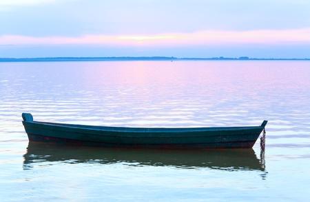 Sunset and old wooden fishing boat on summer lake bank (Svityaz, Ukraine) photo