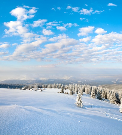 winter calm mountain landscape with sheds group and mount ridge behind (Kukol Mount, Carpathian Mountains, Ukraine)